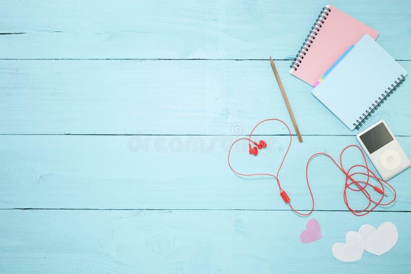 Färgrik pappers- anmärkning med blyertspennan och musikspelaren, röd hörlurnolla royaltyfria foton