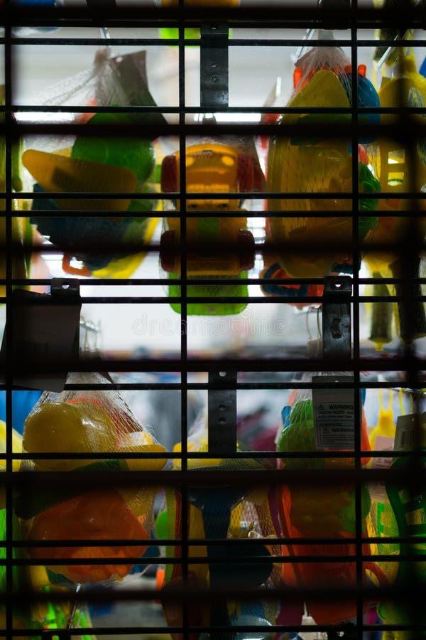 Färgrik plast- leksaker som hänger i en fönsterskärm, bak de stängda portarna av en detaljist, Staten Island, New York royaltyfria foton