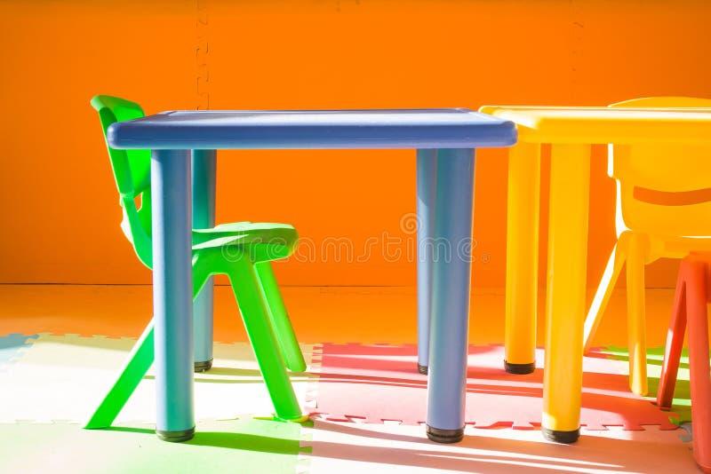 Färgrik plast- stol och skrivbordet för barn som spelar och lär i ungar, hyr rum i tappningstil fotografering för bildbyråer