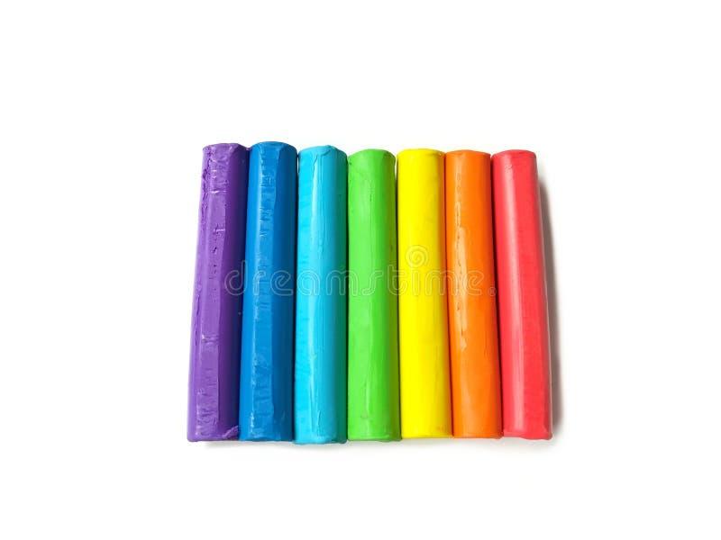 Färgrik plasticine klibbar, den mångfärgade linjen lera, härlig regnbågedeg, vit bakgrund arkivbild