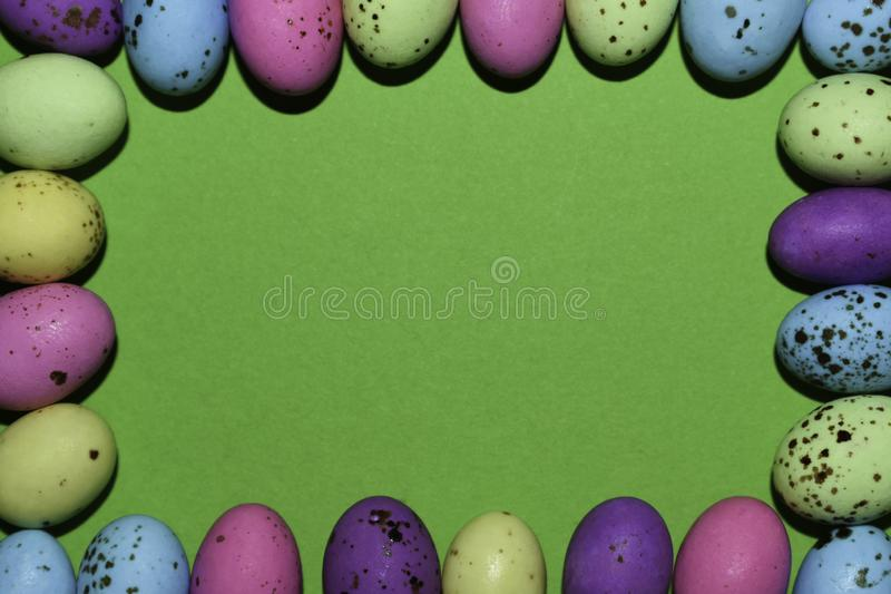 Färgrik ram för godisägg med grönt kopieringsutrymme fotografering för bildbyråer
