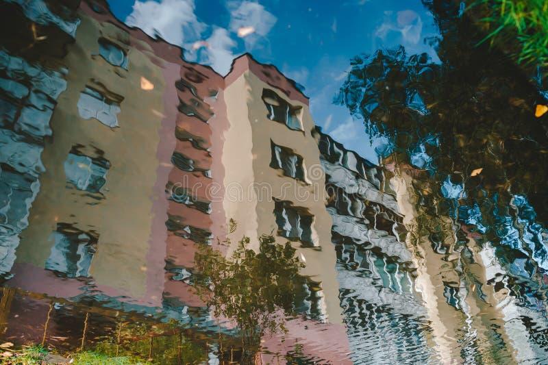 Färgrik reflexion i en pöl av en bostads- byggnad för höghus royaltyfri fotografi