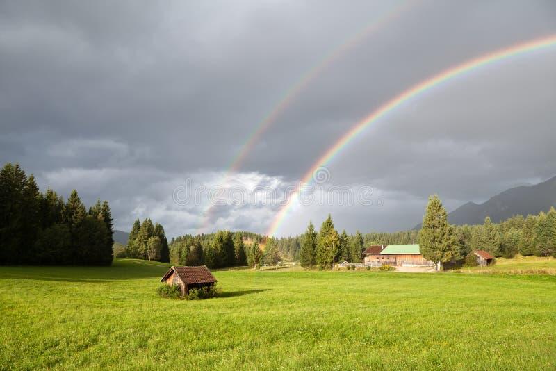 Färgrik regnbåge under regn i fjällängar royaltyfri fotografi