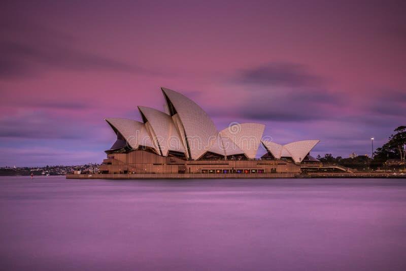Färgrik rosa himmel ovanför härlig operahus arkivfoto
