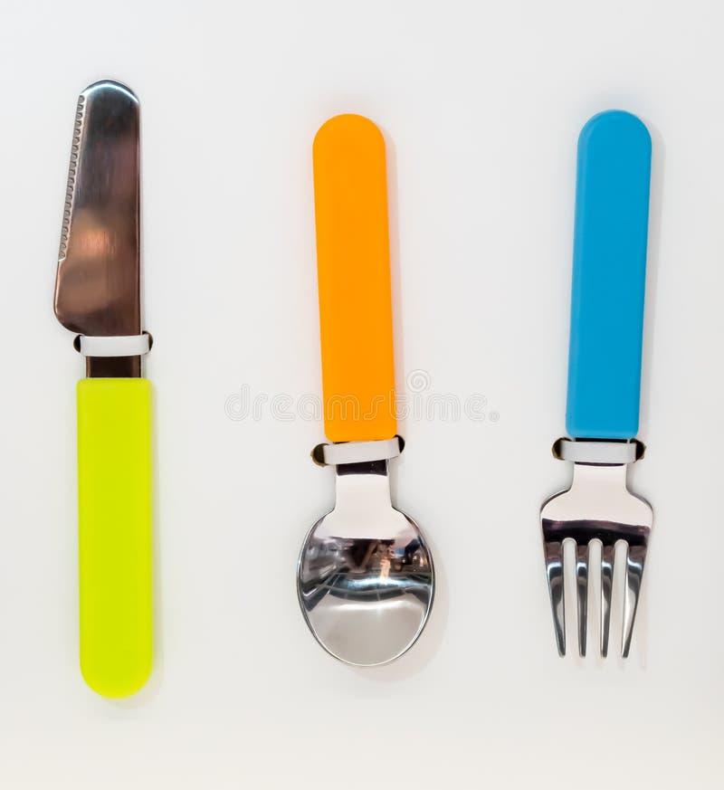 Färgrik rostfri sked, gaffel och kniv royaltyfri fotografi