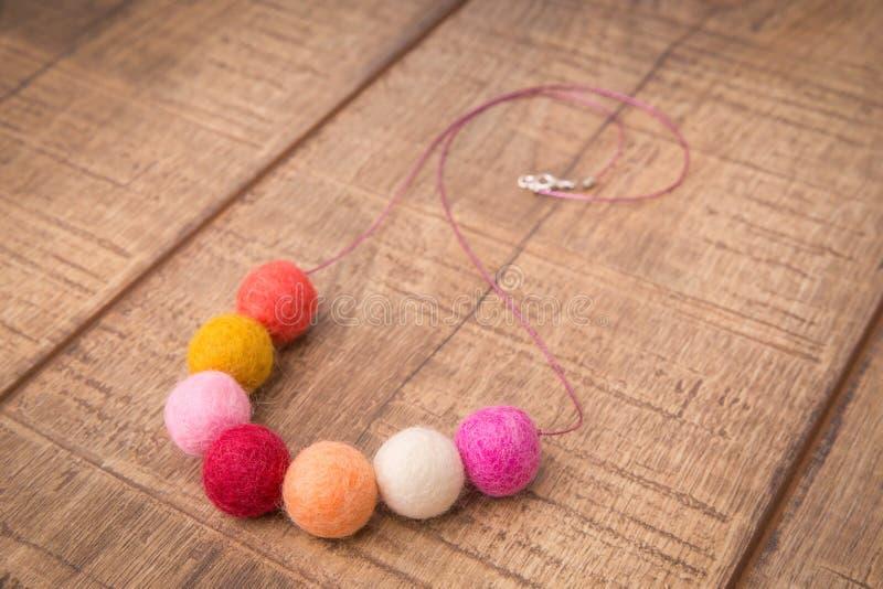 Färgrik rund ullfilt pryder med pärlor halsbandet som är handgjord med för rosa färger, röda, orange och peachy färgpärlor för vi arkivbild