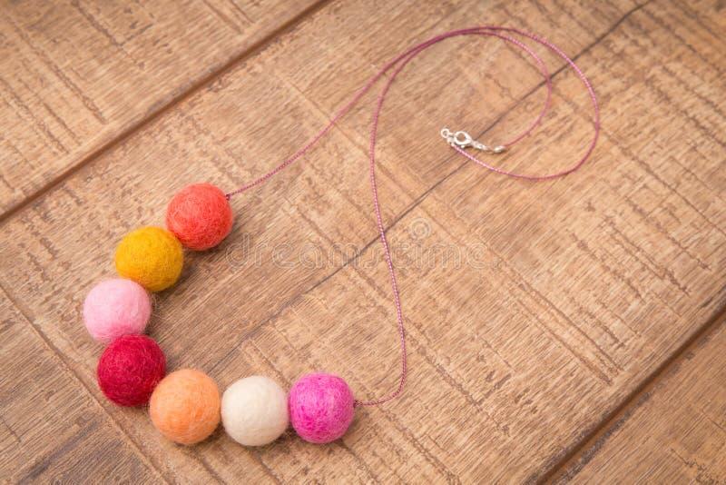 Färgrik runt halsband för trä- och ullfiltpärlor som är handgjord med guld- och gula färgpärlor för rosa färger, på en wood table fotografering för bildbyråer