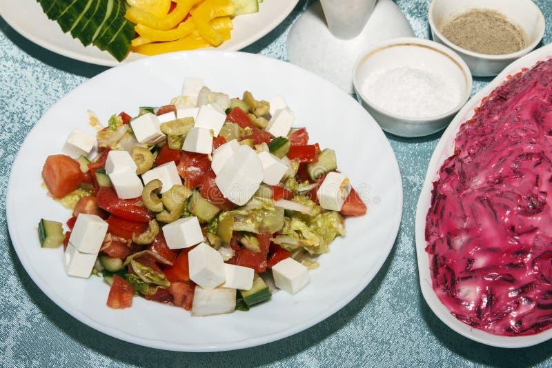 Färgrik sallad av nya organiska grönsaker på den vita plattacloseupen Kall aptitretare för gäster på banketttabellen Sund matconc royaltyfria foton