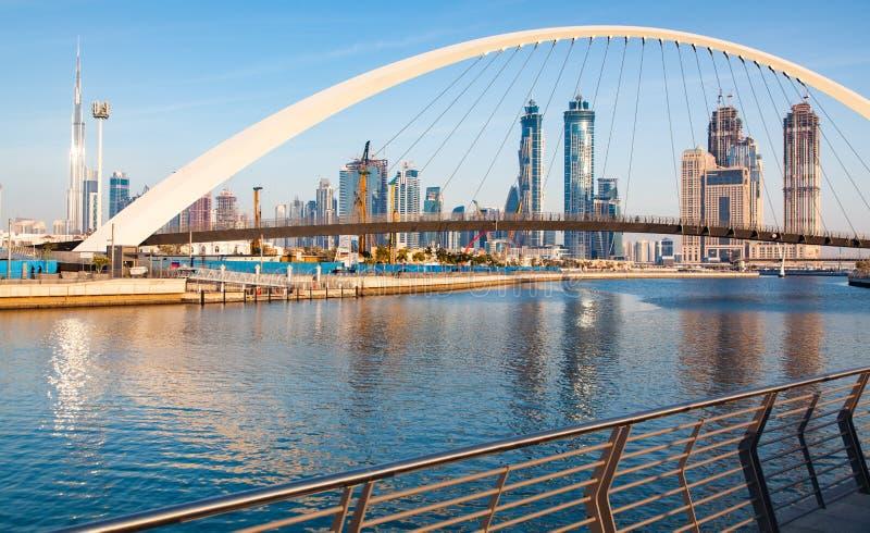 färgrik solnedgång över Dubai i stadens centrum skyskrapor och den nybyggda toleransbron som beskådad från den Dubai vattenkanale royaltyfria foton