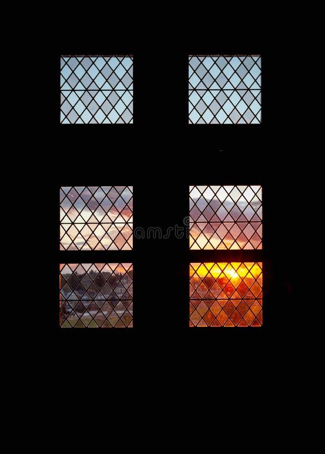 Färgrik solnedgång bak tappningfönster arkivbilder