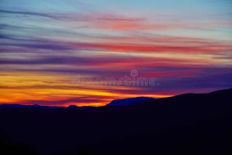 Färgrik solnedgång och kontur av berglandskapet arkivfoto