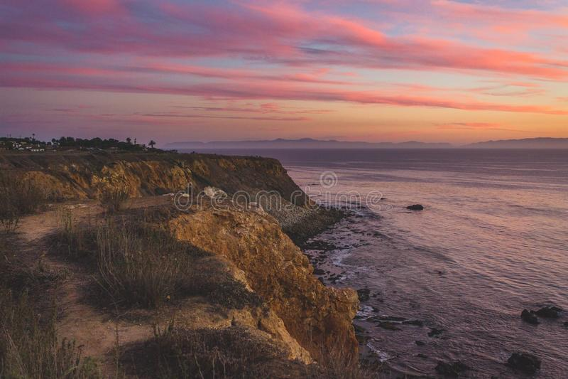 Färgrik solnedgång på den guld- lilla viken arkivbilder