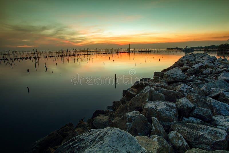 Färgrik solnedgånghimmel på den övergav havscoastaen i bangpoosamuthpra arkivfoton