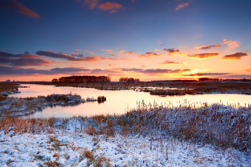 Färgrik soluppgång över floden i vinter arkivbilder