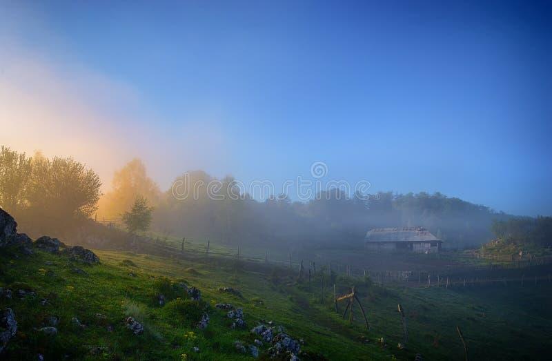 Färgrik soluppgång i en Carpathian dal för dimmigt berg med det gamla trähuset royaltyfria bilder