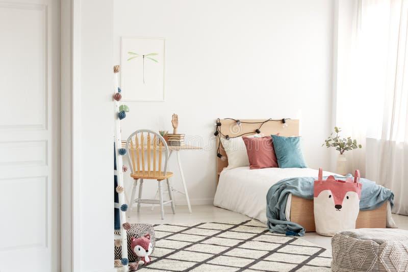 Färgrik sovrumdesign för tonåring, enkel träsäng och skrivbord med böcker fotografering för bildbyråer