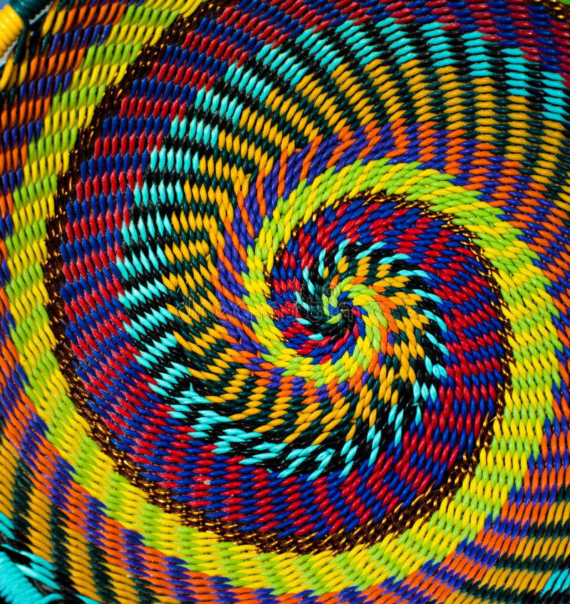 Färgrik spiral modell på botten av en vävd trådkorg fotografering för bildbyråer