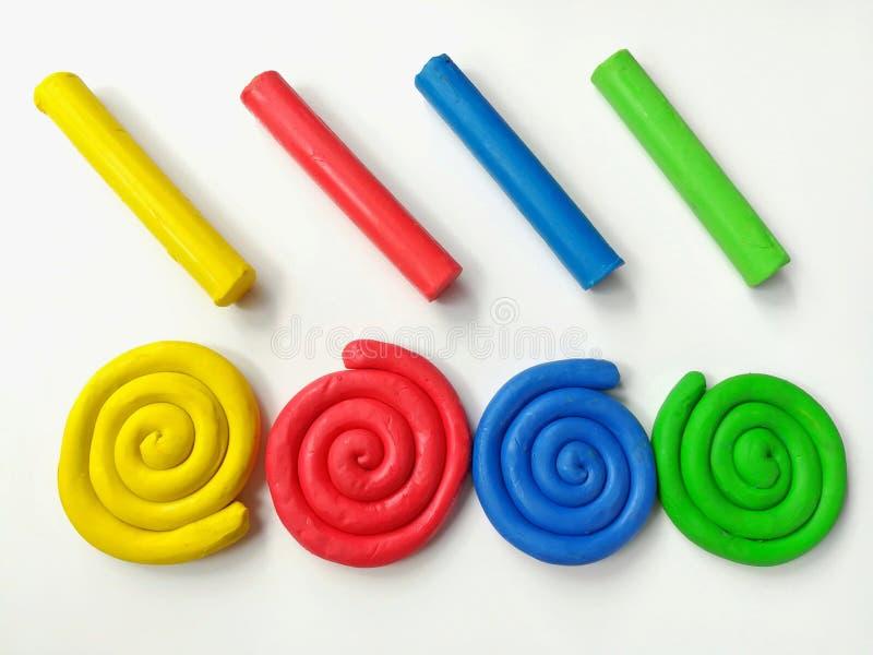 Färgrik spiral plasticine, mångfärgad pinneleradeg, vit bakgrund royaltyfri foto