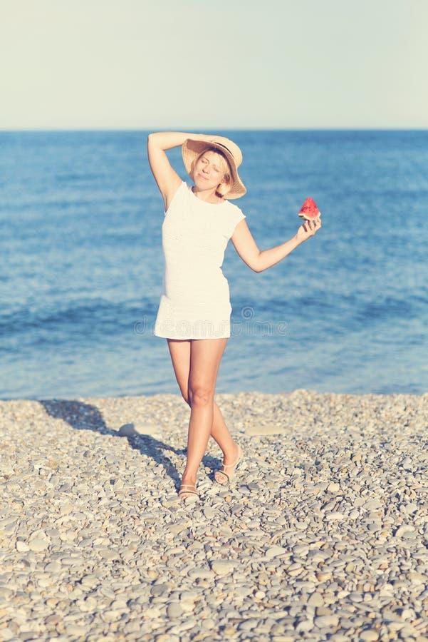 Färgrik stående av flickainnehavvattenmelon på en härlig tropisk strand arkivfoto