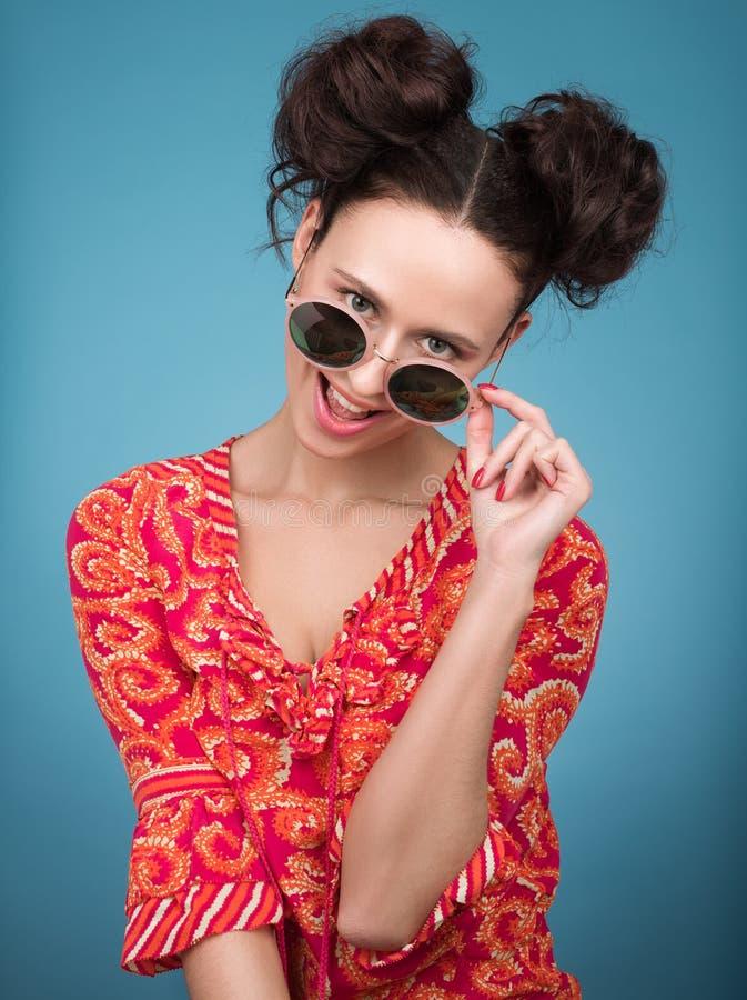 Färgrik studiostående av den gladlynta unga kvinnan i solglasögon Ljus röd blus royaltyfria foton