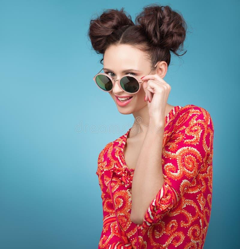 Färgrik studiostående av den härliga unga kvinnan som poserar i solglasögon En stilfull frisyr arkivbild