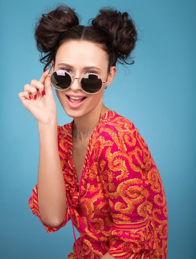 Färgrik studiostående av den härliga unga kvinnan som poserar i solglasögon stort leende arkivbild