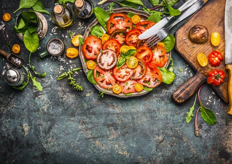 Färgrik tomatsalladförberedelse med skärbrädan, plattan och bestick, bästa sikt royaltyfri bild