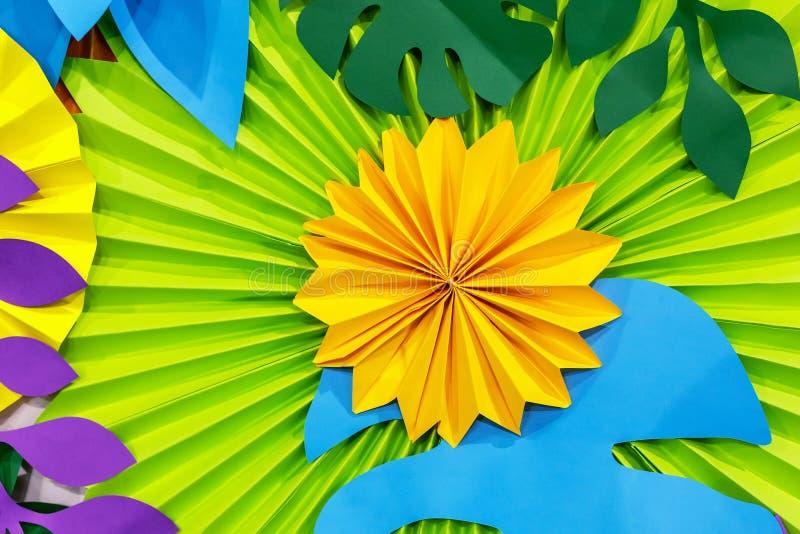 Färgrik tropisk bakgrund för pappers- blomma mångfärgade blommor och sidor som göras av papper arkivfoto