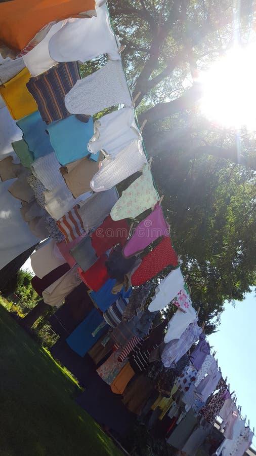 Färgrik tvätteri som hänger på en kläderlinje för att torka i solen arkivbild