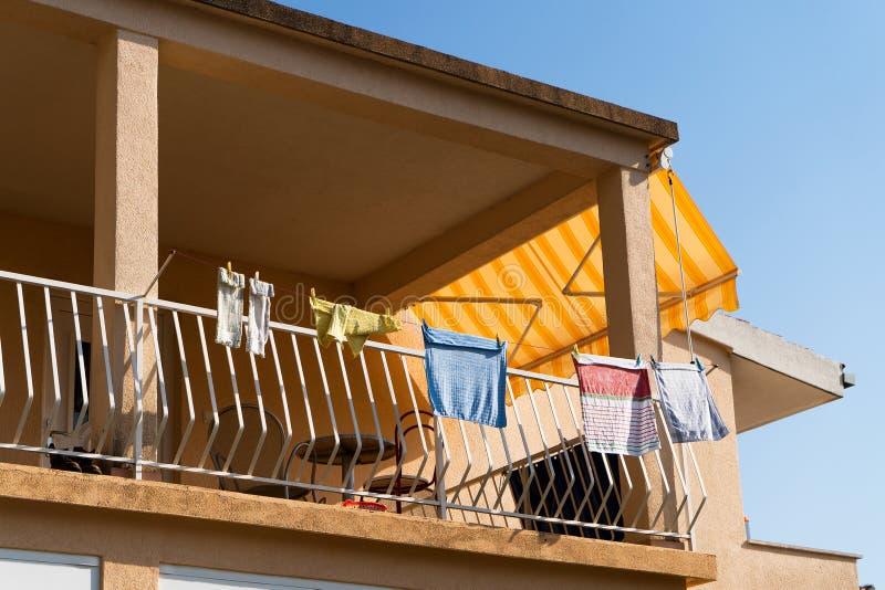 Färgrik tvätteri som torkar på balkong med blå himmel på bakgrund royaltyfri foto