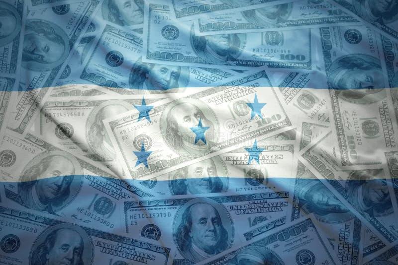 Färgrik vinkande honduranflagga på en dollarpengarbakgrund royaltyfria foton