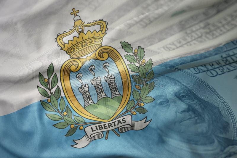 Färgrik vinkande nationsflagga av San Marino på en amerikansk dollarpengarbakgrund royaltyfri fotografi