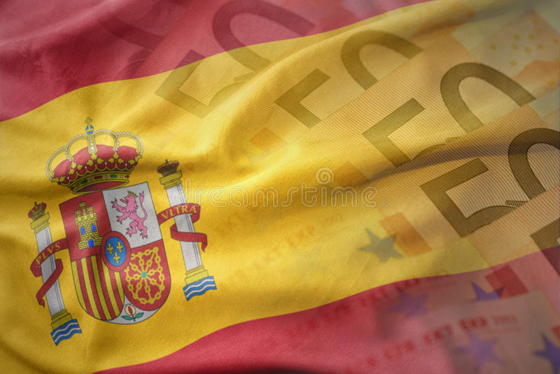 Färgrik vinkande nationsflagga av Spanien på en bakgrund för europengarsedlar arkivfoto