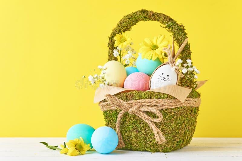 Färgrika ägg för påsk i korg med blommagarneringar på en gul bakgrund royaltyfria bilder