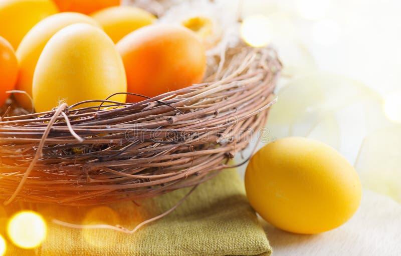 Färgrika ägg för påsk i målade den rede härliga färgrika gulingen och orange färgägg med garneringar på den vita trätabellen arkivbilder
