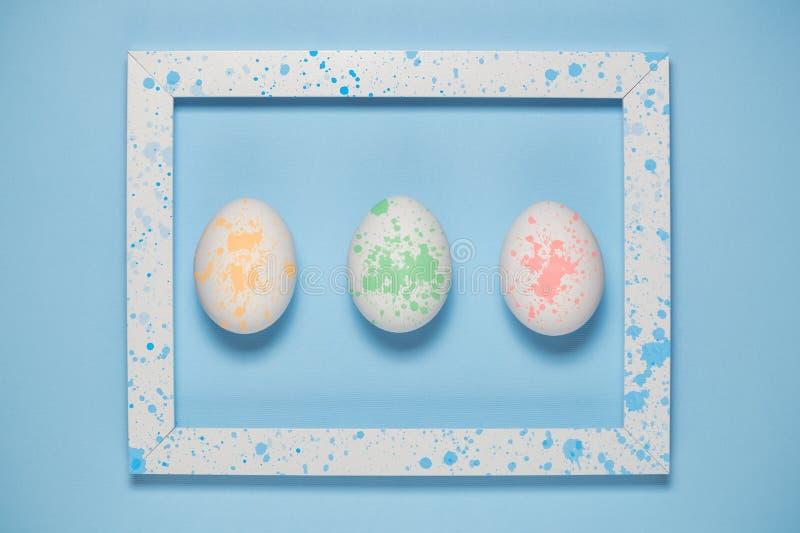 Färgrika ägg och den konstnärliga ramen på slätten slösar bakgrund royaltyfri fotografi