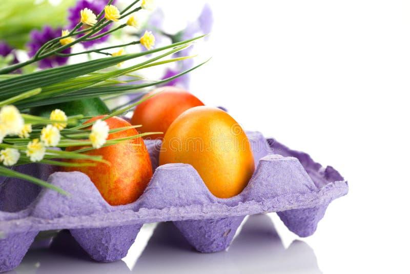 Färgrika ägg och grupp av blommor arkivbild