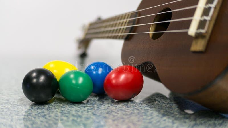 Färgrika äggshaker med ukulelet för mörk brunt royaltyfria foton