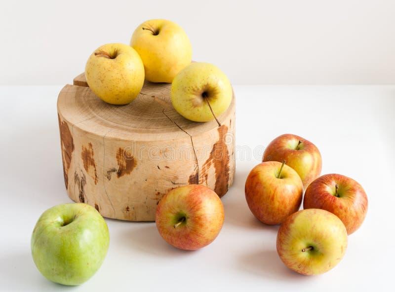 Färgrika äpplen på den vita tabellen och på trästubbe arkivbilder