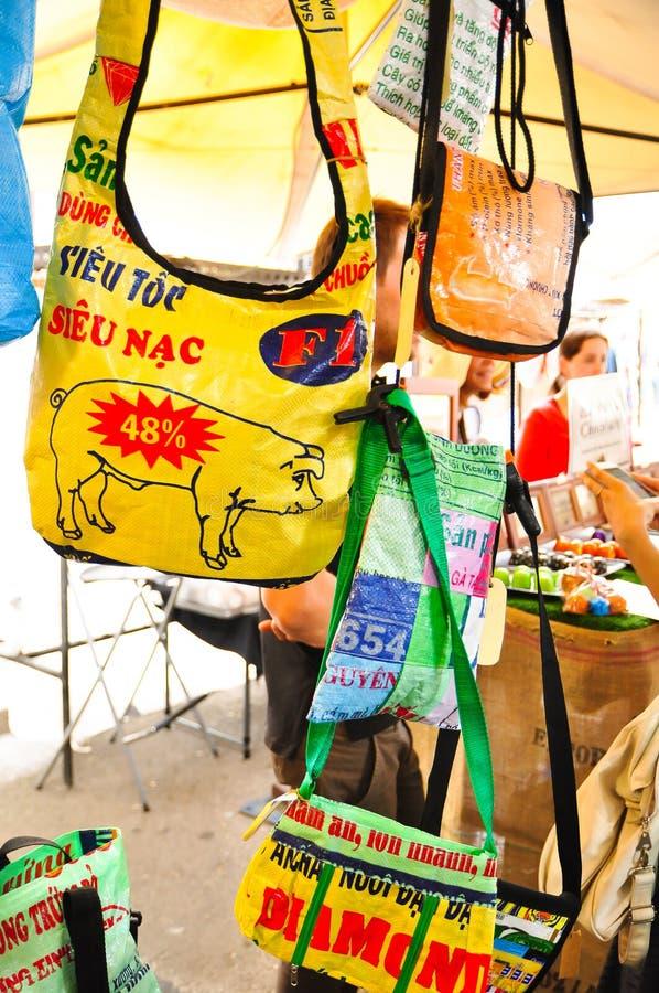 Färgrika återvinningpåsar som produceras från den plast- säcken som är till salu på söndag, marknadsför, vaggar arkivfoto