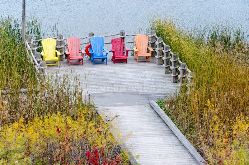 Färgrika Adirondack stolar i den Muskoka semesterorten arkivfoto