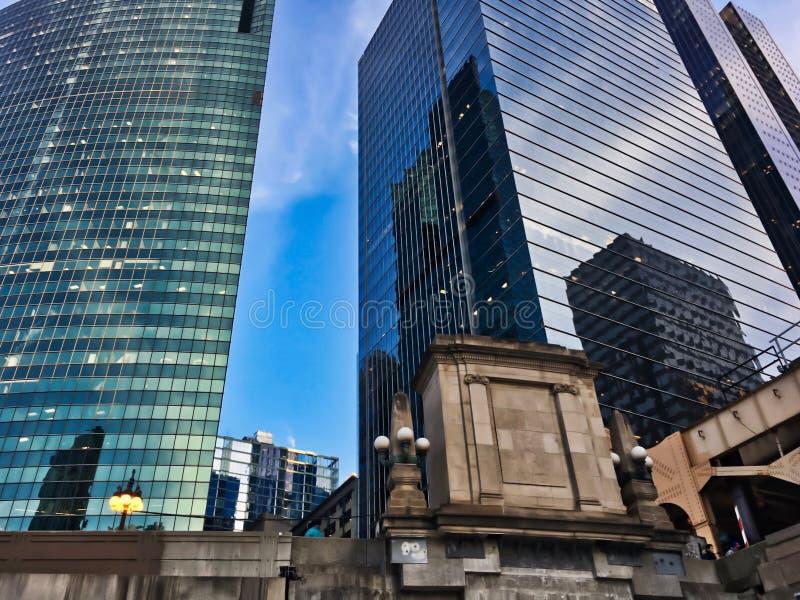 Färgrika aftonfärger reflekteras i cityscape för Chicago ` s under vinterrusningstidpendlingssträcka royaltyfria foton