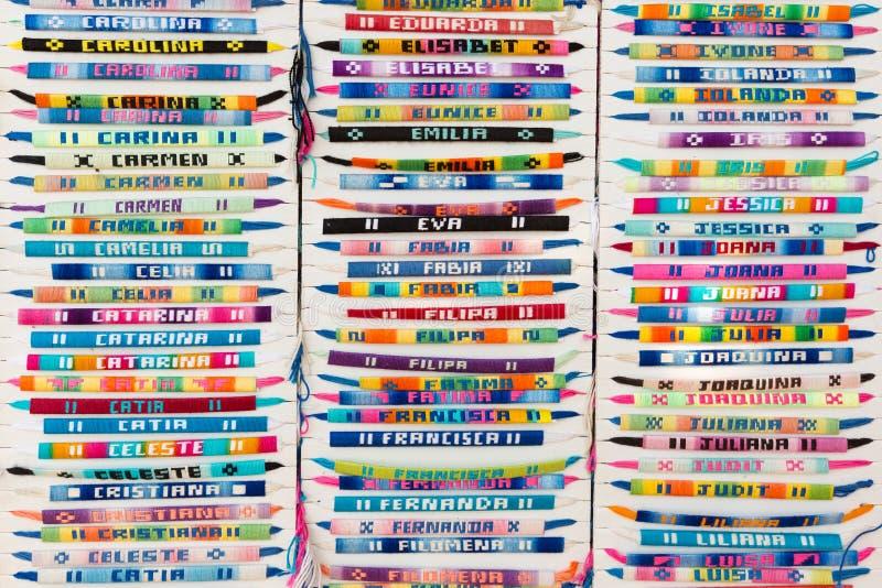 Färgrika armarmband med broderade namn arkivbild