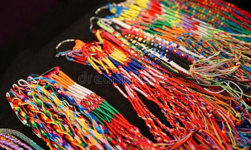 Färgrika armringar och färgrik tråd för halsband arkivbild