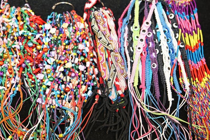 Färgrika armringar och halsband binder producerat av en hantverkare arkivbilder