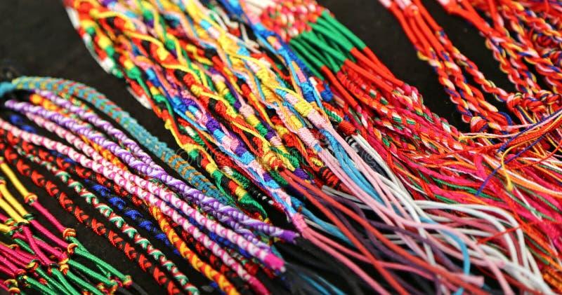Färgrika armringar och halsband binder producerat av en sakkunnig craftsm royaltyfria foton