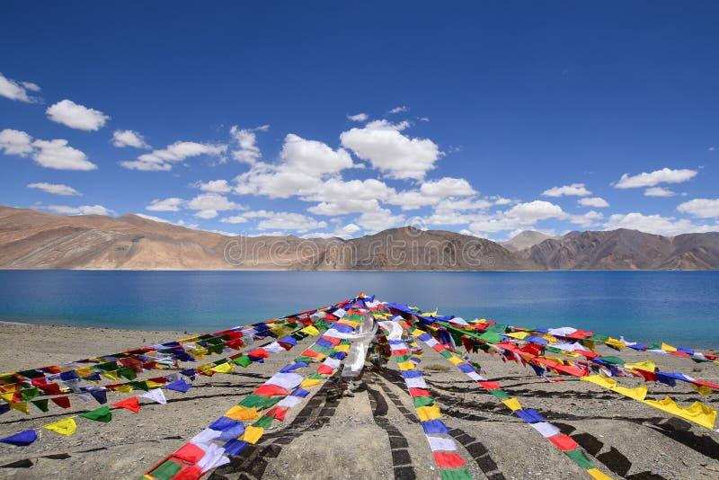 Färgrika bönflaggor hänger framme av Pangong sjön arkivfoton
