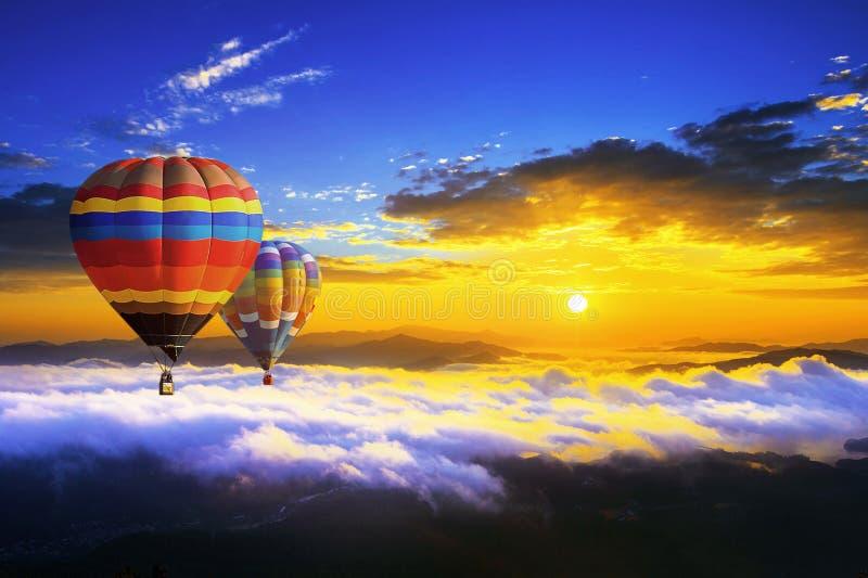 Färgrika ballonger för varm luft som flyger över berget som täckas vid morgon, fördunklar på soluppgång royaltyfri foto