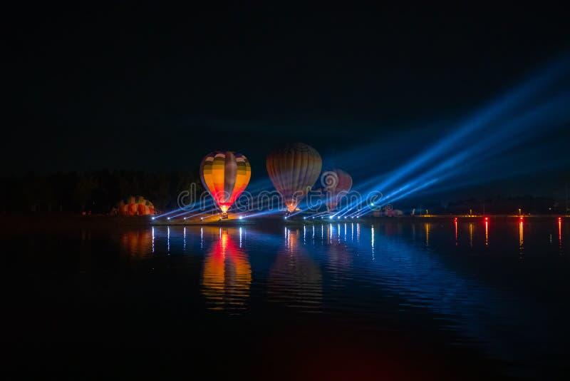 Färgrika ballonger för varm luft som flyger över floden på nattfestival fotografering för bildbyråer