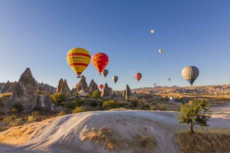 Färgrika ballonger för varm luft som flyger över forntida dalar royaltyfri foto